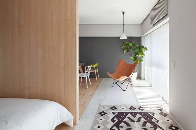 Một không gian thư giãn với cây xanh và chiếc ghế bành cách điệu ngay cạnh cửa vô cùng lý tưởng cho gia chủ.