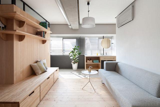 Không gian phòng khách được bố trí đơn giản với ghế sofa dài và chiếc bàn 3 chân nhỏ gọn.